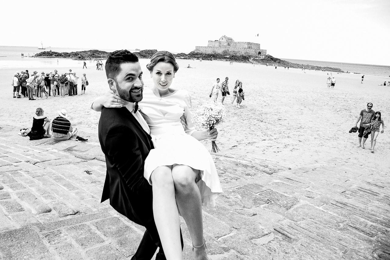 Mariée dans les bras du marié sur une plage à Saint Malo