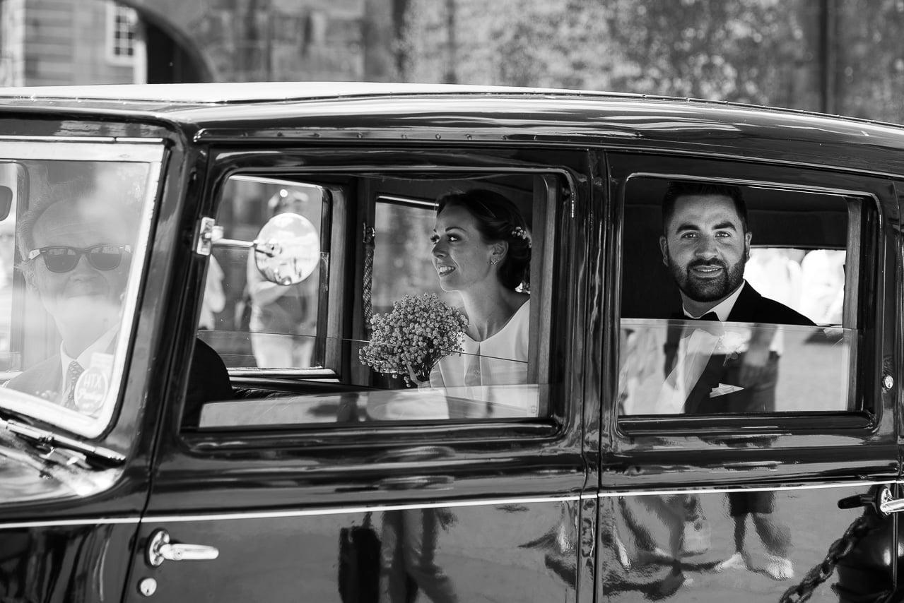 Les mariés dans leur élégante voiture ancienne