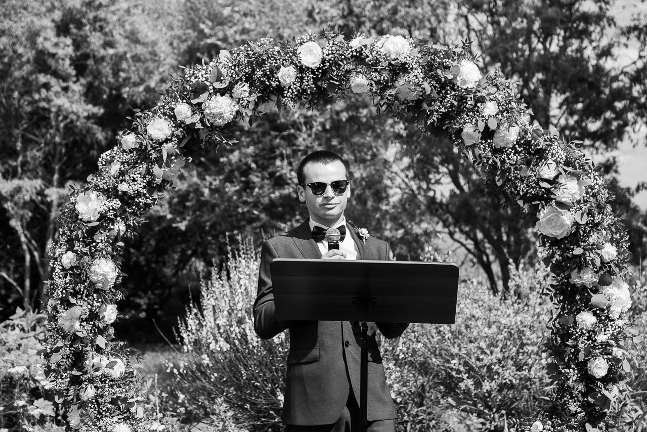 Marié entouré d'une arche de fleurs