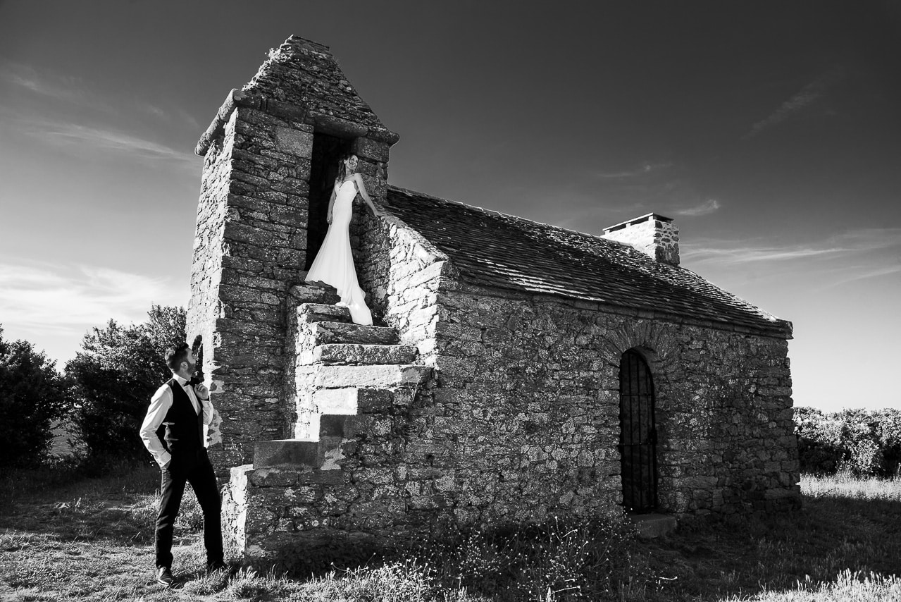 Les mariés posant sur un petit batiment en pierre