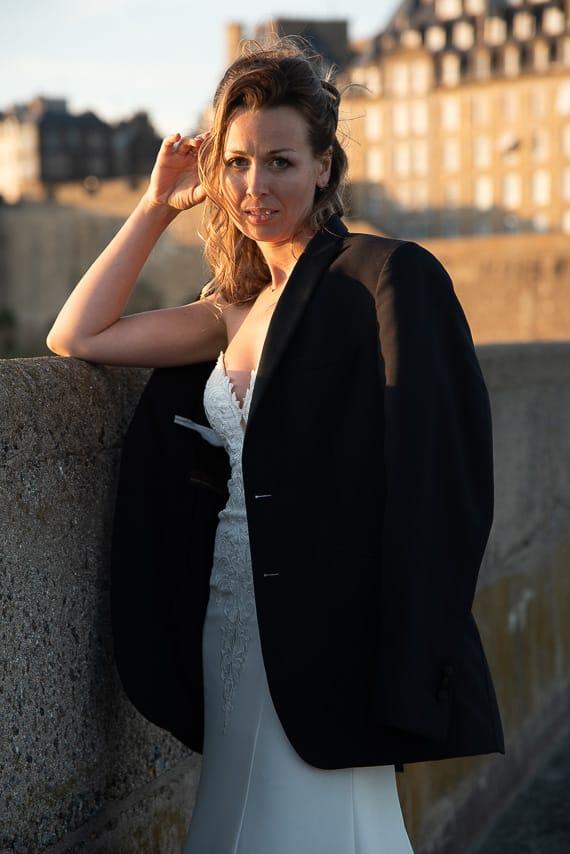 Mariée sur les remparts avec la veste de costume noir du marié
