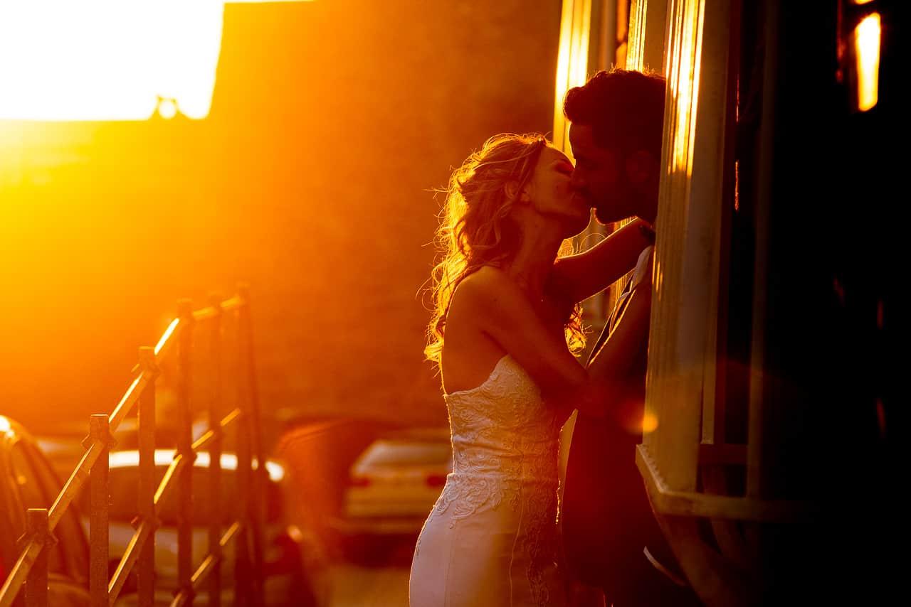 Mariés s'embrassant avec un magnifique coucher de soleil