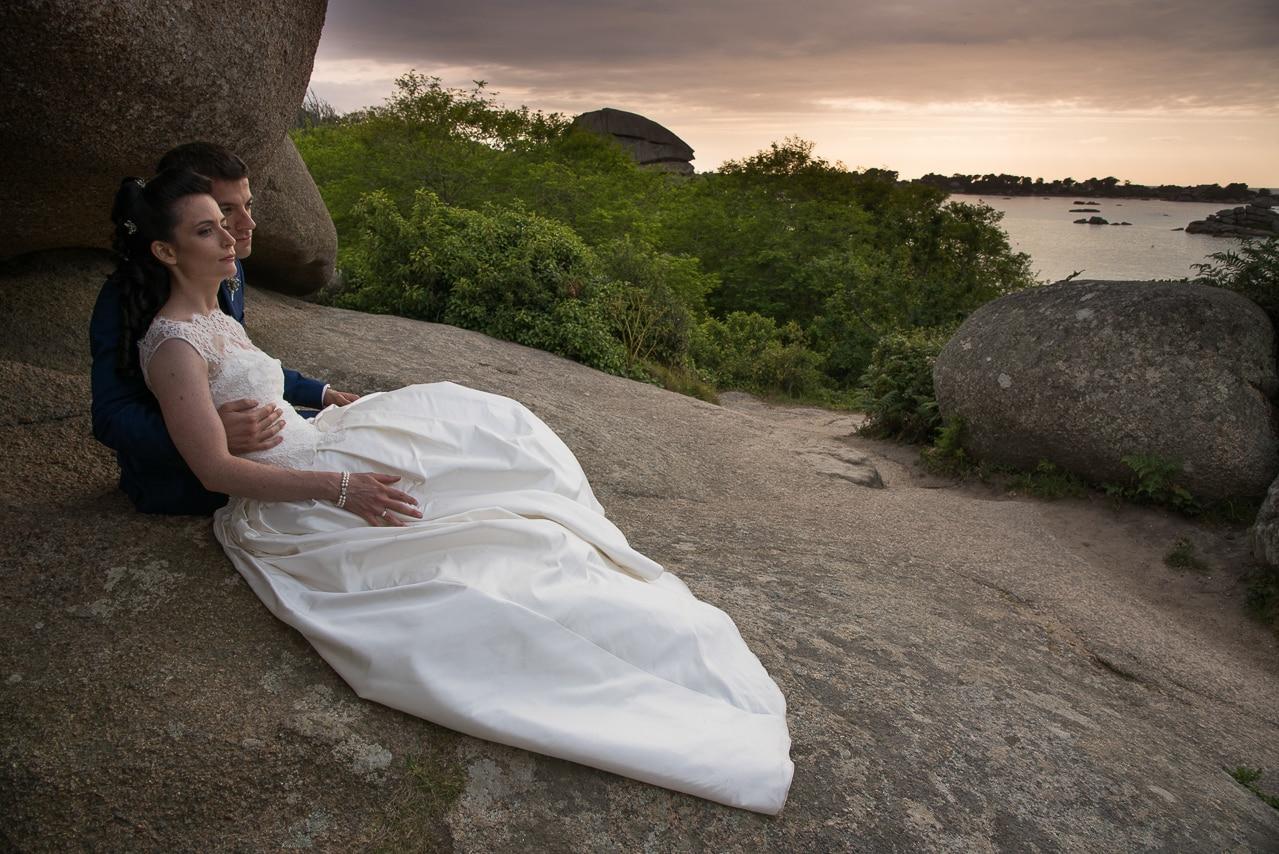 Mariés posant sur les rôchers devant la mer