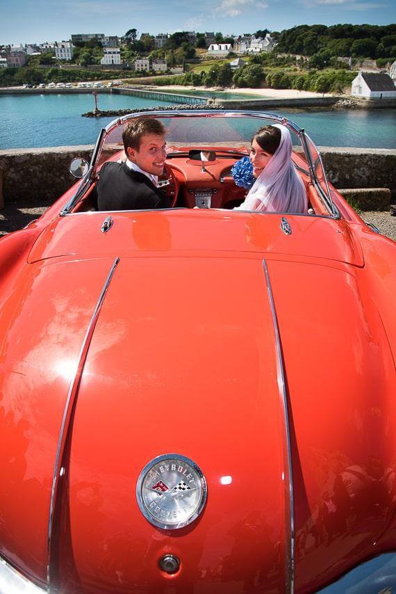 Les mariés au bord de mer dans leur voiture