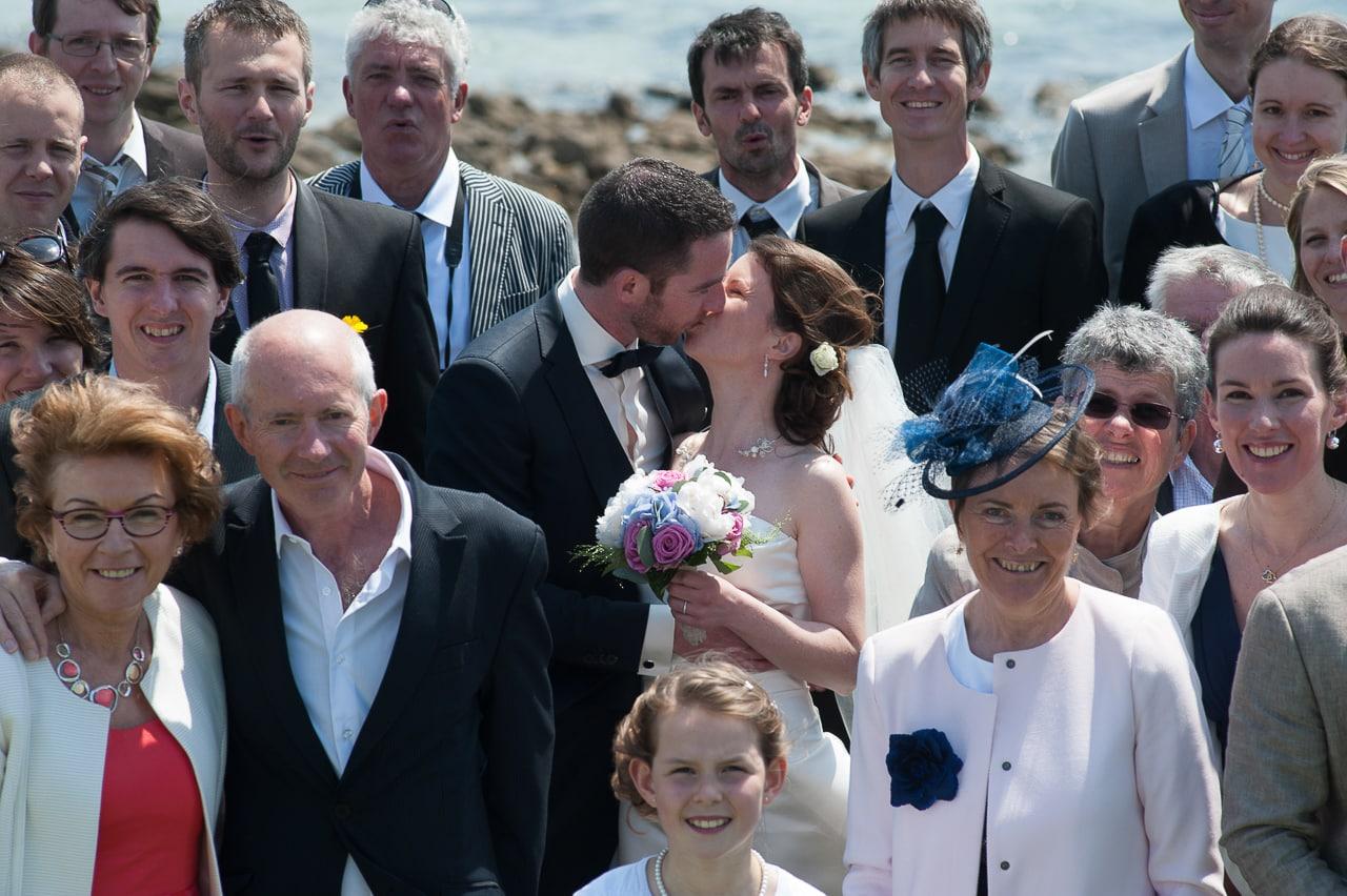Les mariés s'embrassant entourés de leurs convives