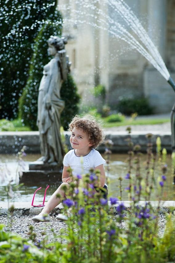 Une petite fille assise au bord de la fontaine