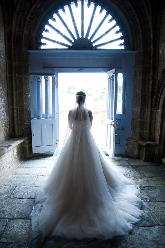 Mariée avec son longue robe blanche davant la porte de l'église