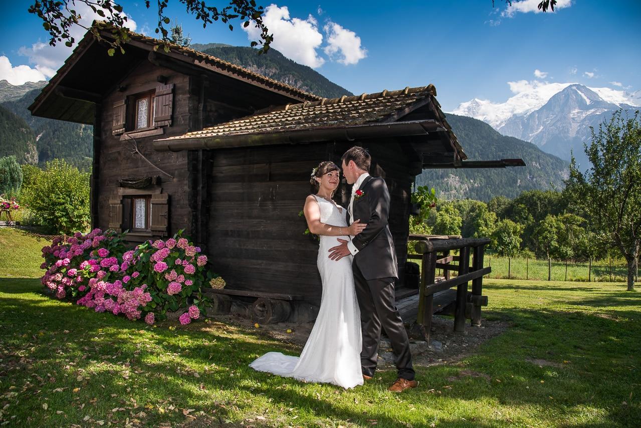Mariée dans les bras du marié derrière un  chalet en bois