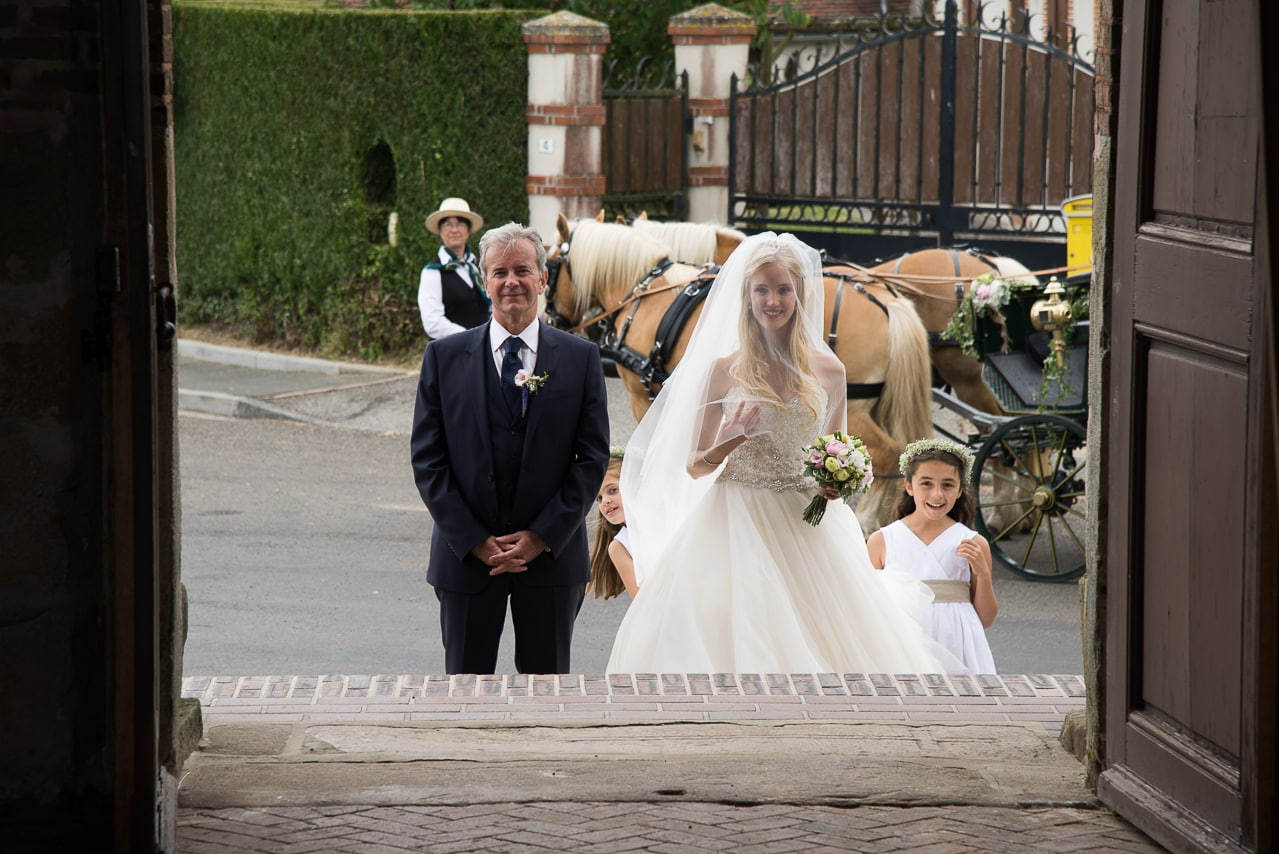 Mariée accompagnée de son père  devant l'église