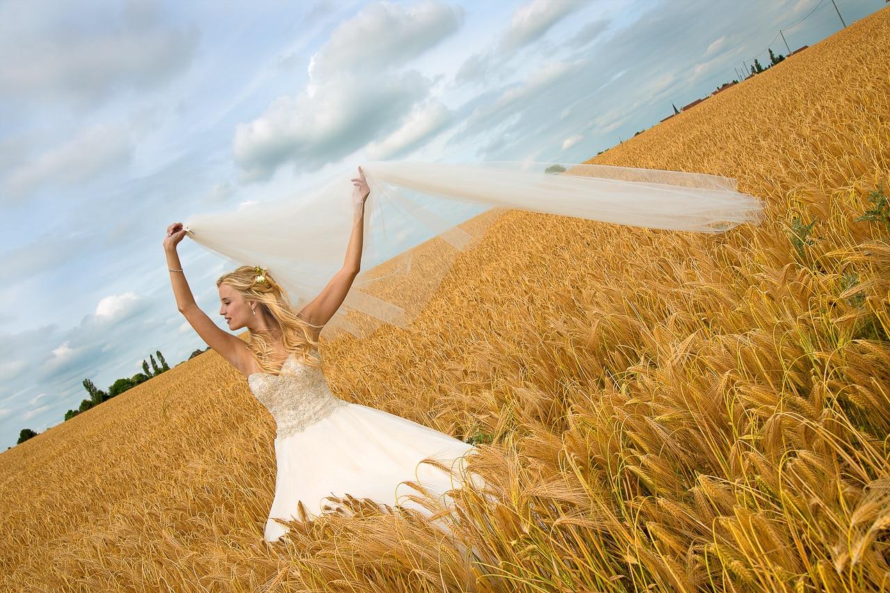 Mariée dans un champ avec son voile  en l'air