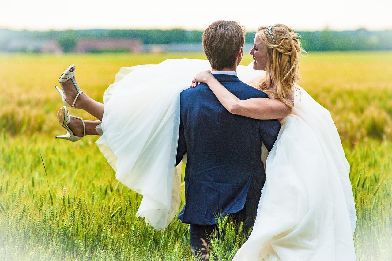 Mariée dans les bras du marié dans un  champ de blé