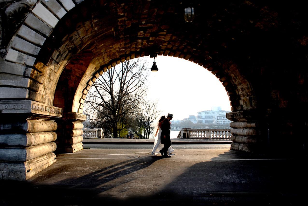 Mariés se tenant la main sous un pont