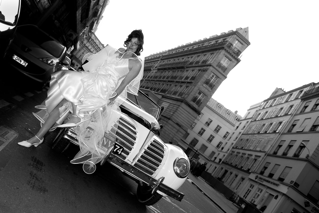 Mariée dans Paris près de sa voiture de mariage