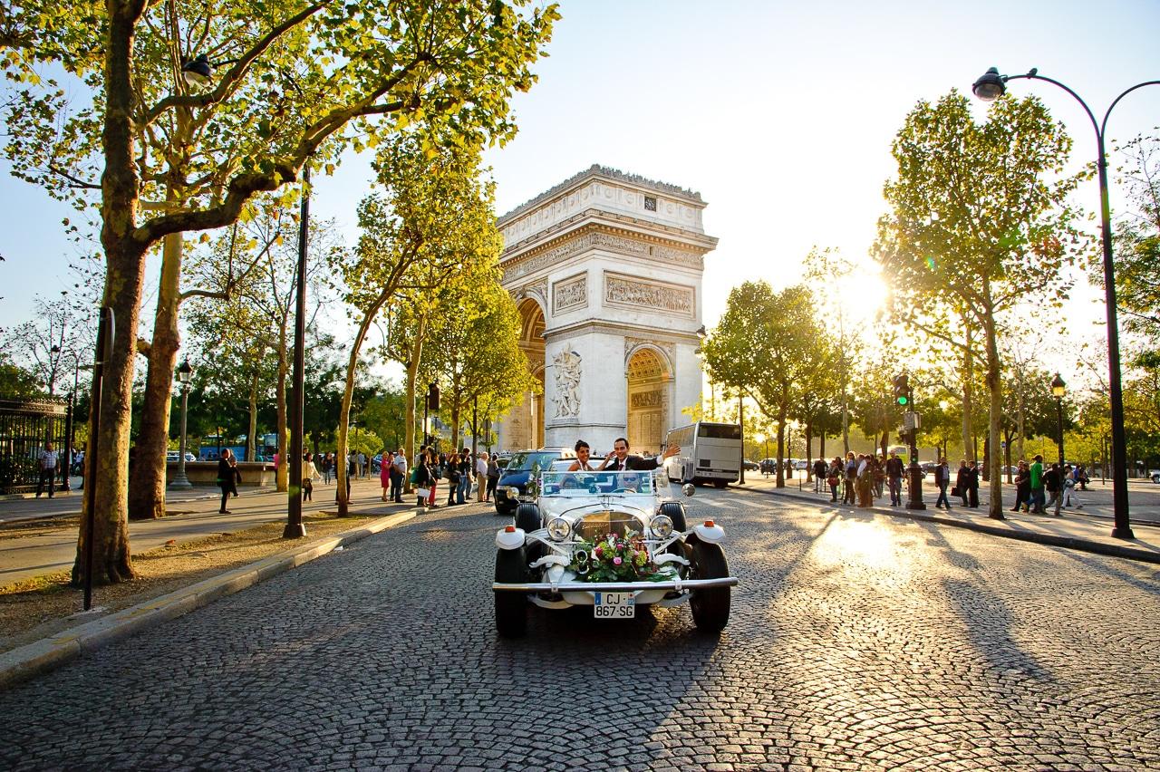 Mariés dans leur voiture spéctaculaire devant l'Arc de Triomphe