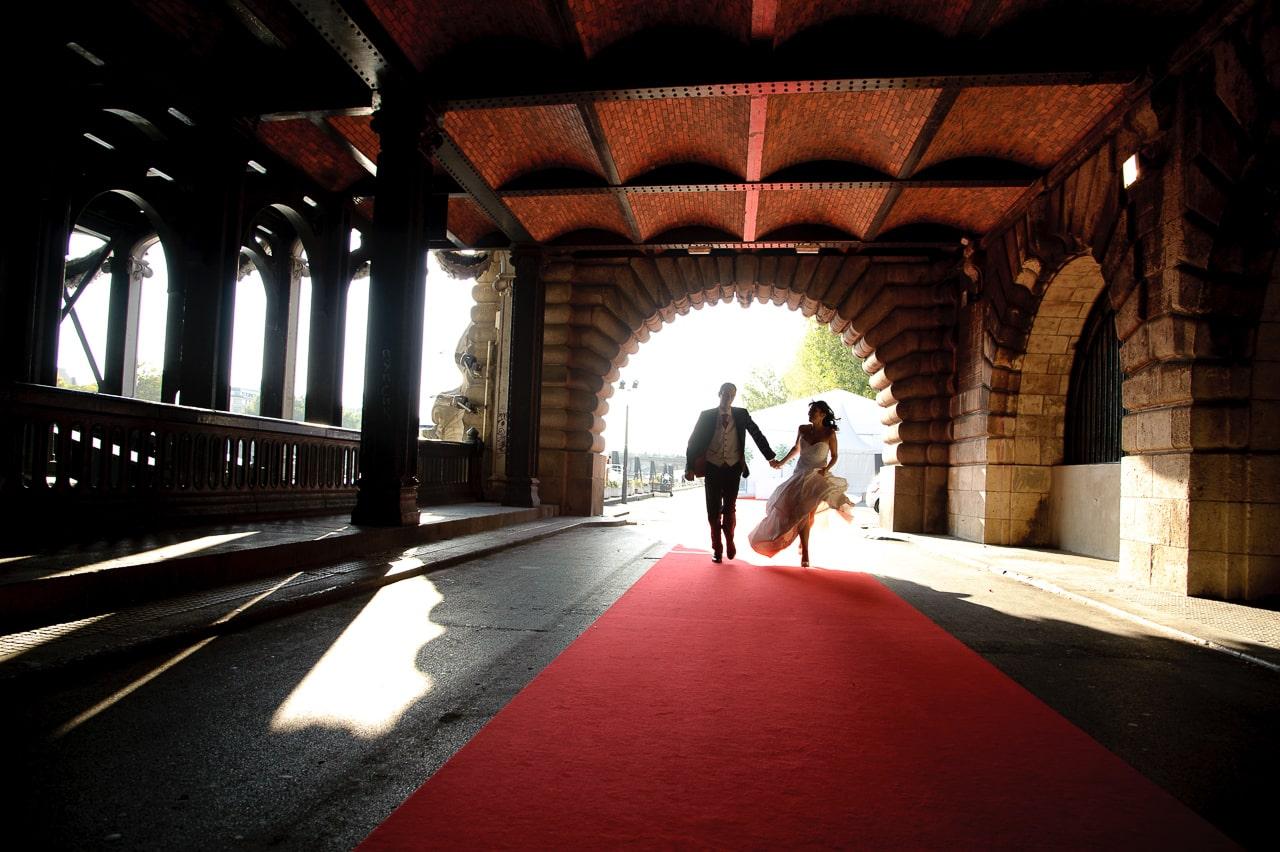 Mariés courant vers le photographe dans Paris sur un tapis rouge