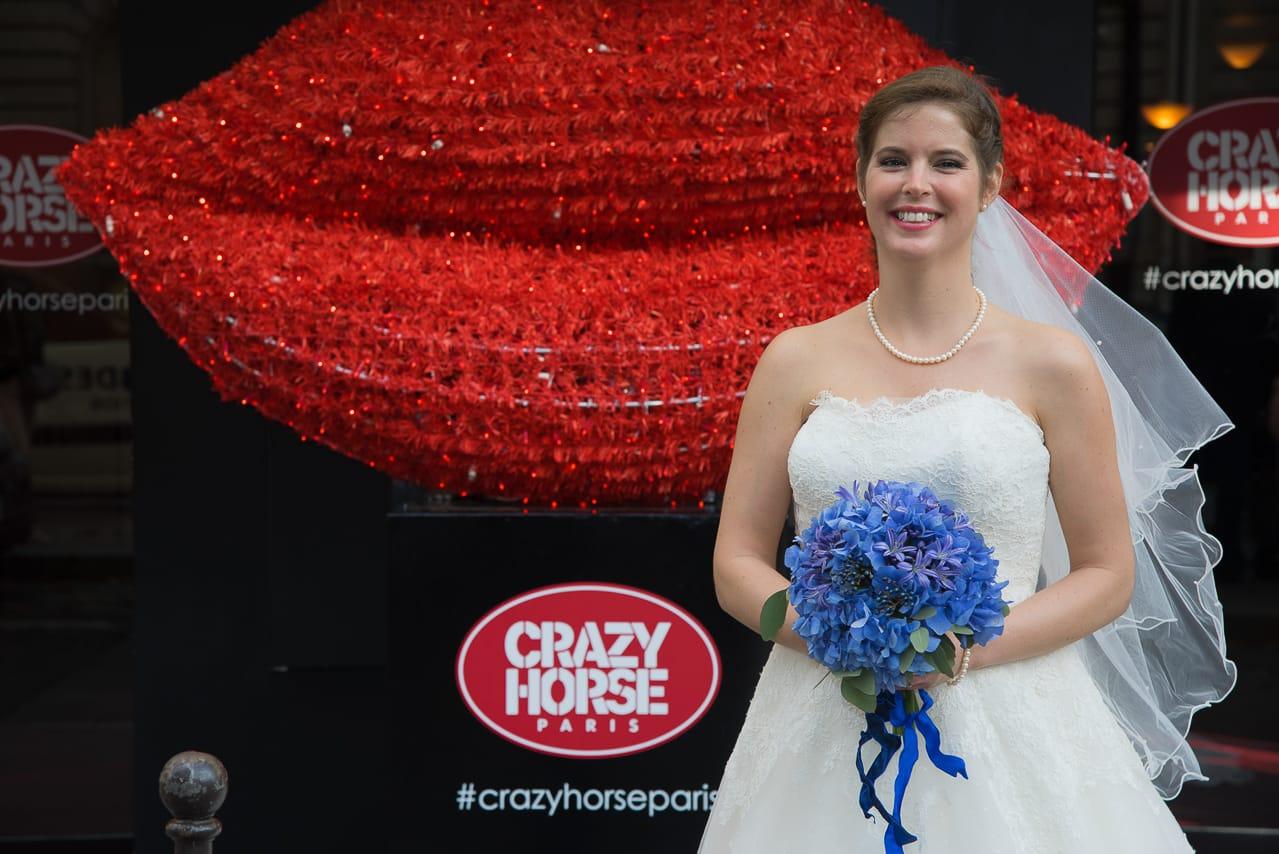 La magnifique mariée et son bouquet bleu devant le Crazy Horse