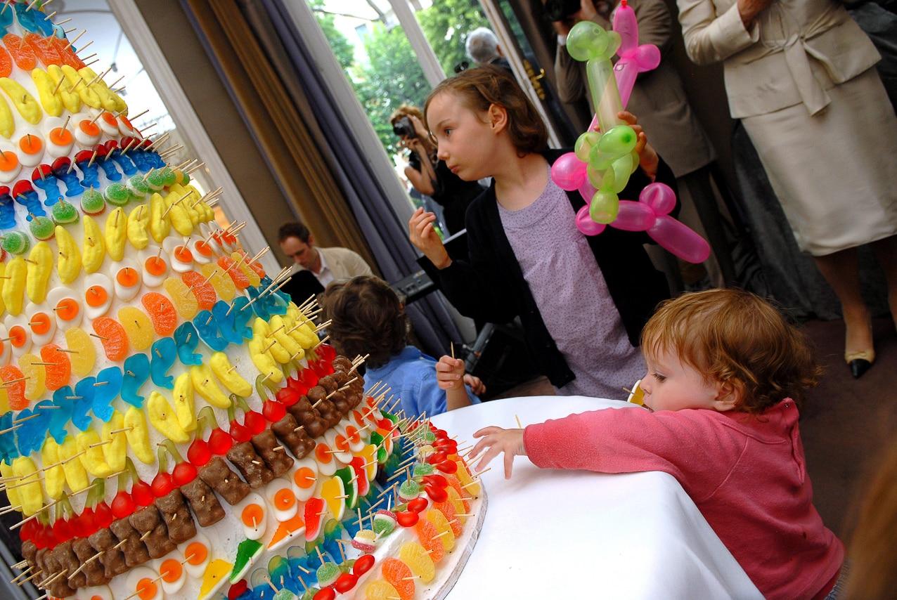 Les enfants dans la salle de réception autour du gâteau de bonbons