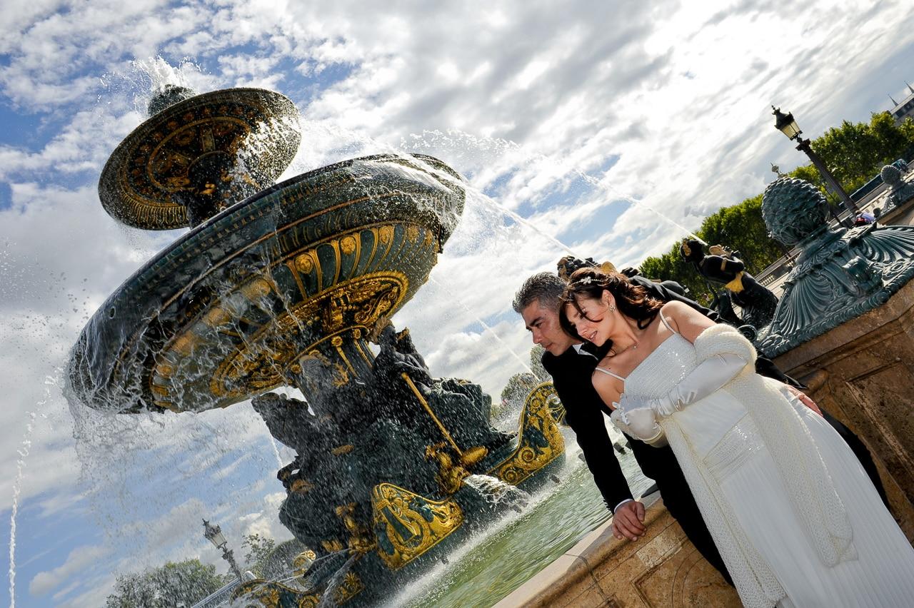 Les mariés devant une fontaine à Paris