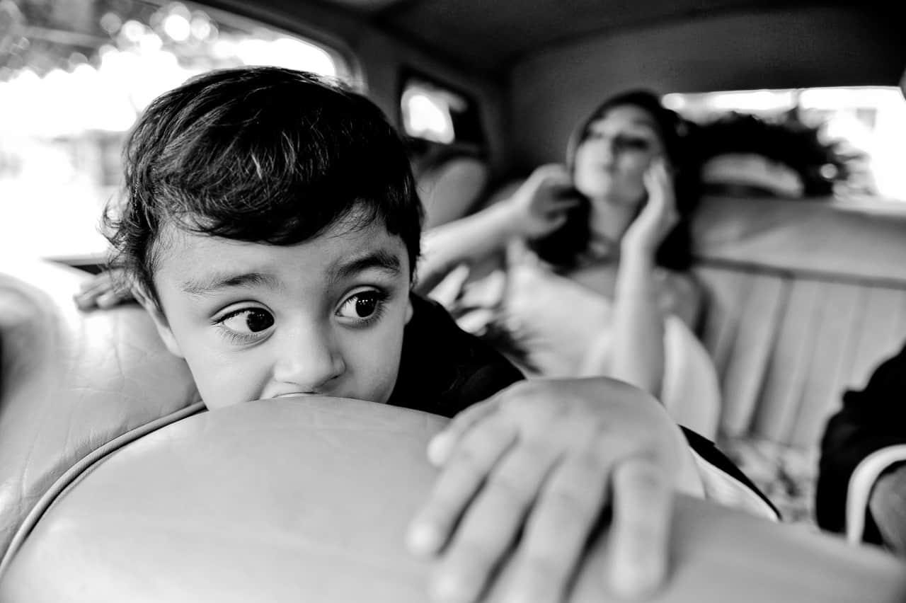 Petit garçon à l'arrière de la voiture des mariés