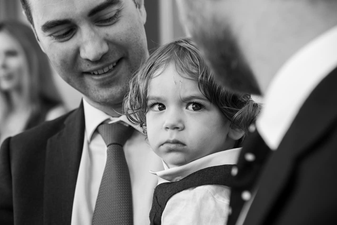 Enfant dans les bras d'un invité du mariage