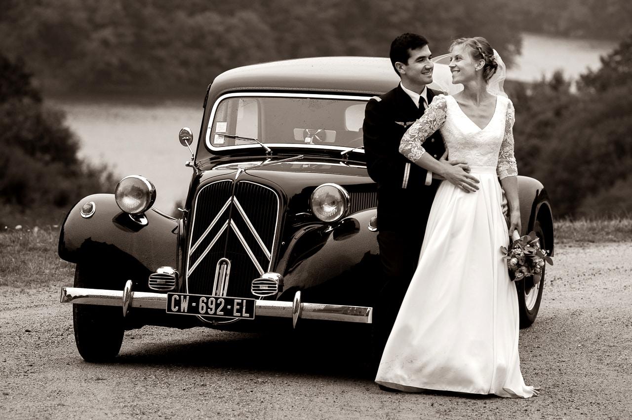 Mariés prenant la pose devant une traction avant noire