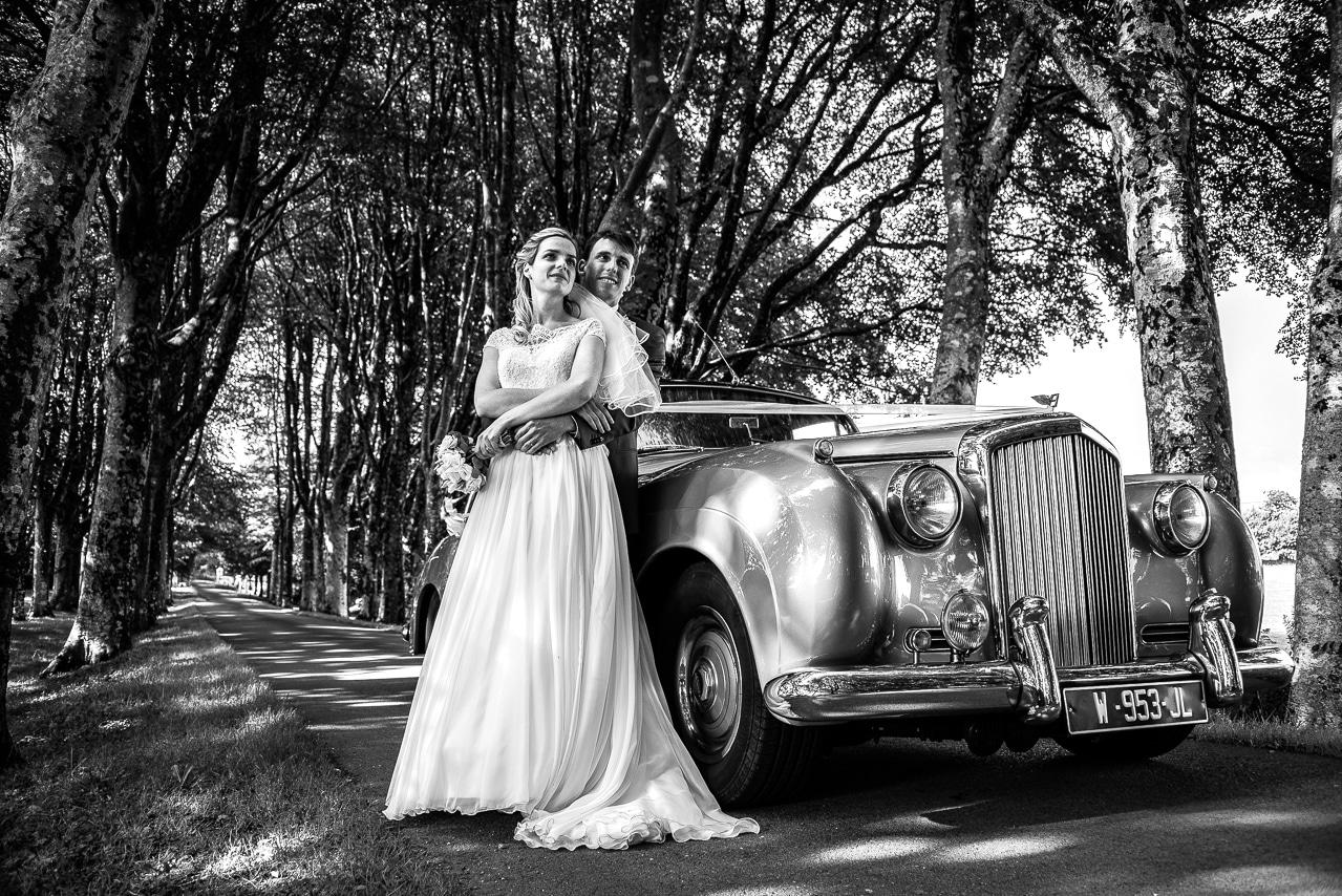 Portrait de mariés en noir et blanc devant une Bentley