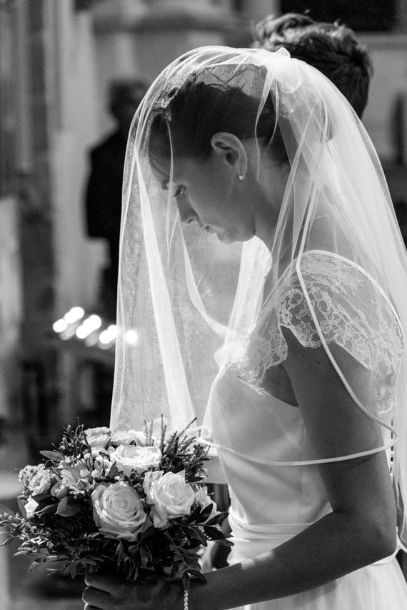 Portrait de mariée dans l'église avec son voile et bouquet a la main