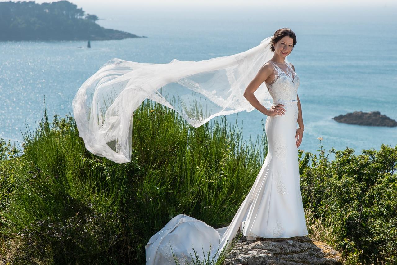 Mariée avec sa longue traine et la mer en arrière plan
