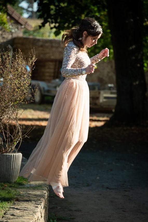 Femme qui saute d'un rebord en pierre pendant  le mariage
