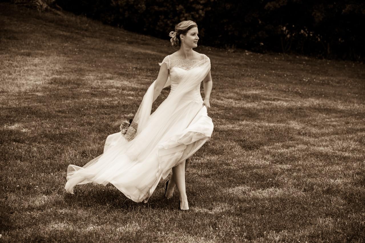 Mariée marchant dans l'herbe avec son magnifique bouquet