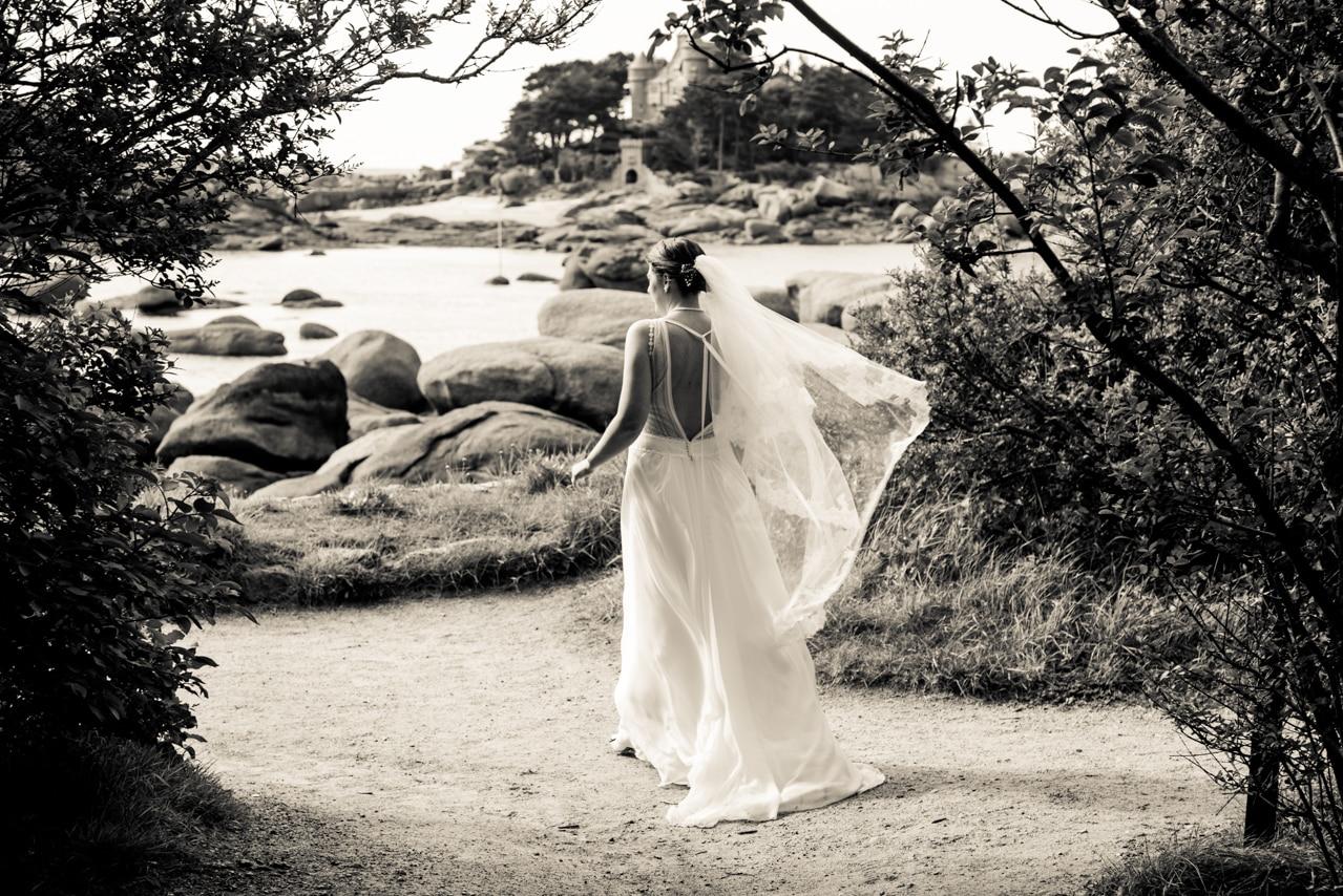 Mariée dans son élégante robe dos nu en dentelle blanche face à la mer
