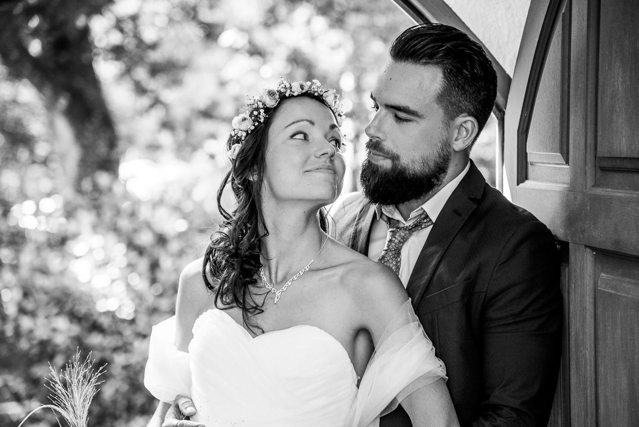 Mariés complices devant une porte en bois