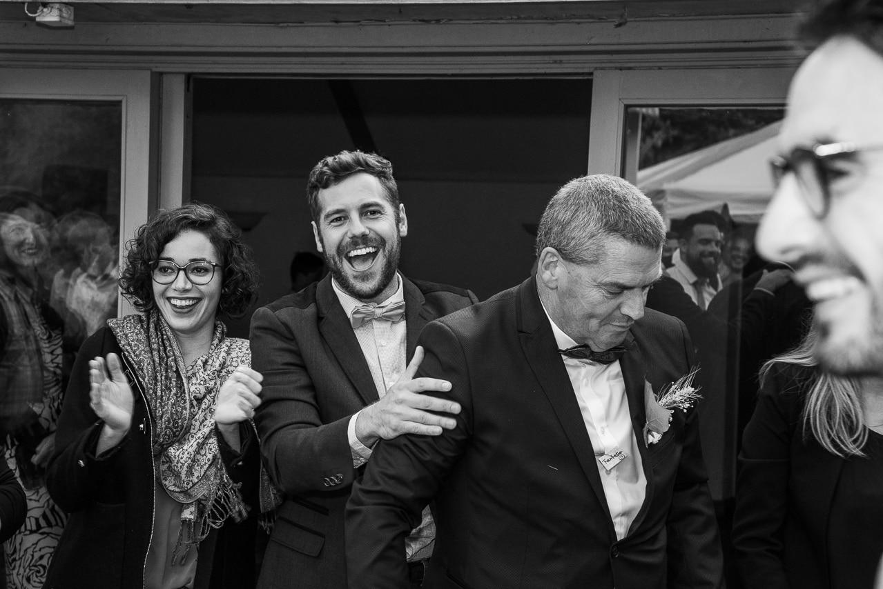 Moment de joie entre le marié et deux convives