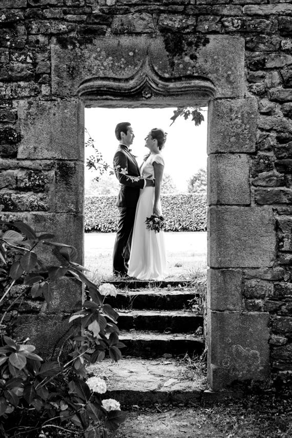 Mariés derrière un mur en pierre