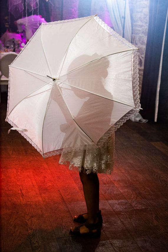 Petite fille sous un parapluie pendant la soirée de mariage