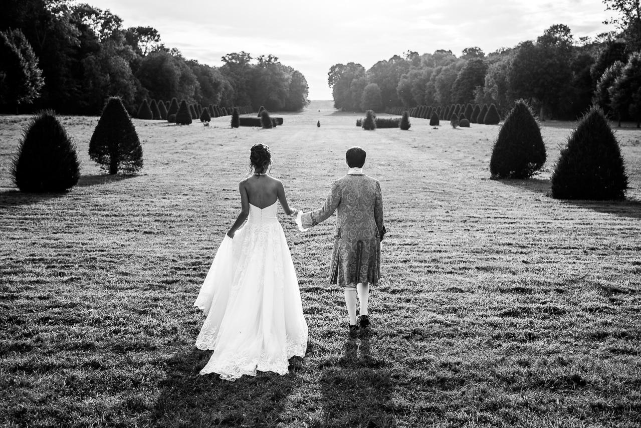 Mariés de dos dans un somptueux jardin
