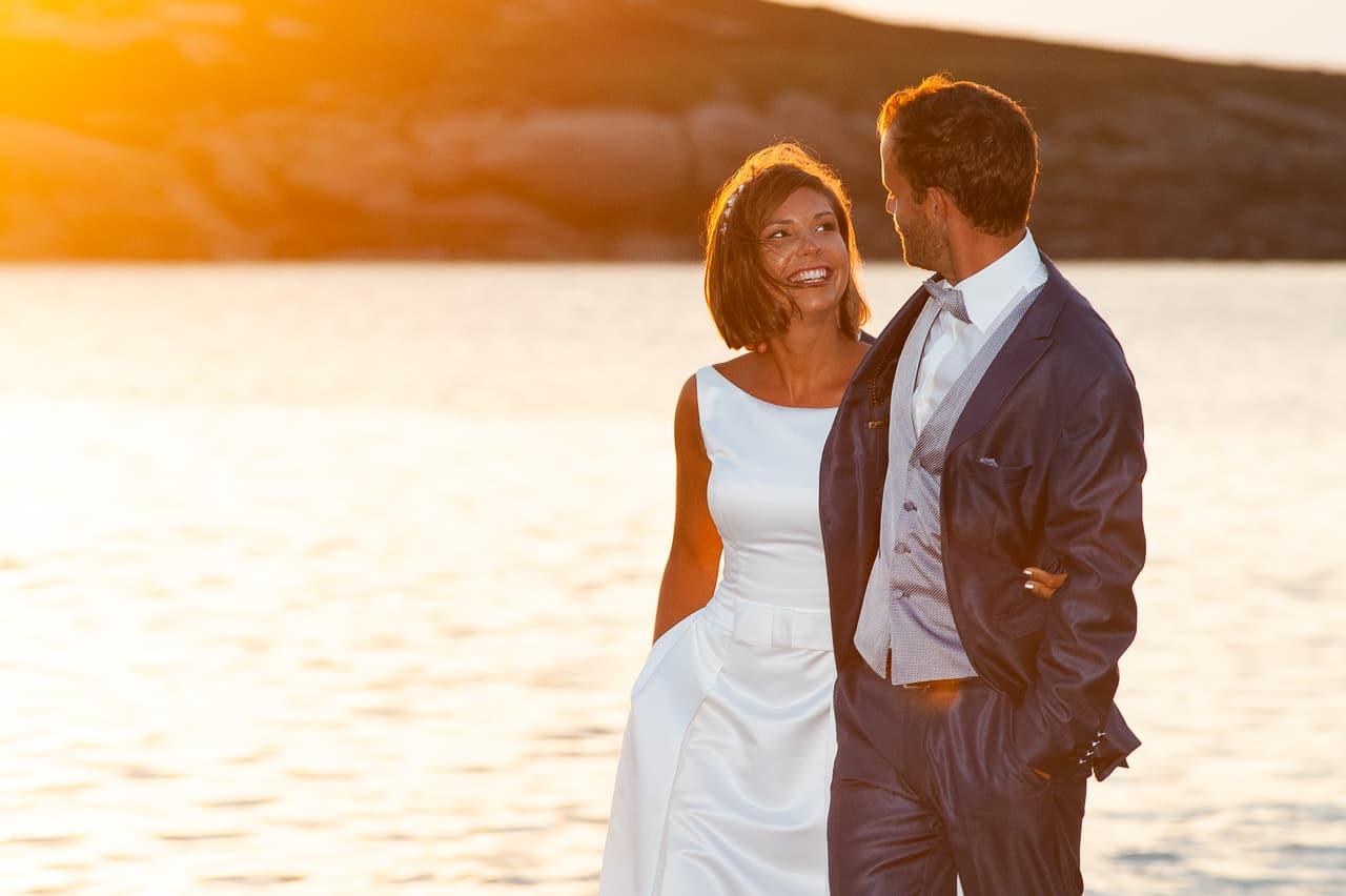 Mariés face à la mer avec coucher de soleil