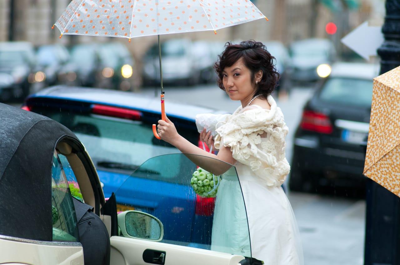 Mariée tenant son parapluie et son bouquet sous la pluie