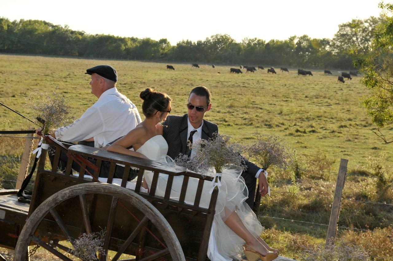 Mariés dans une calèche en bois
