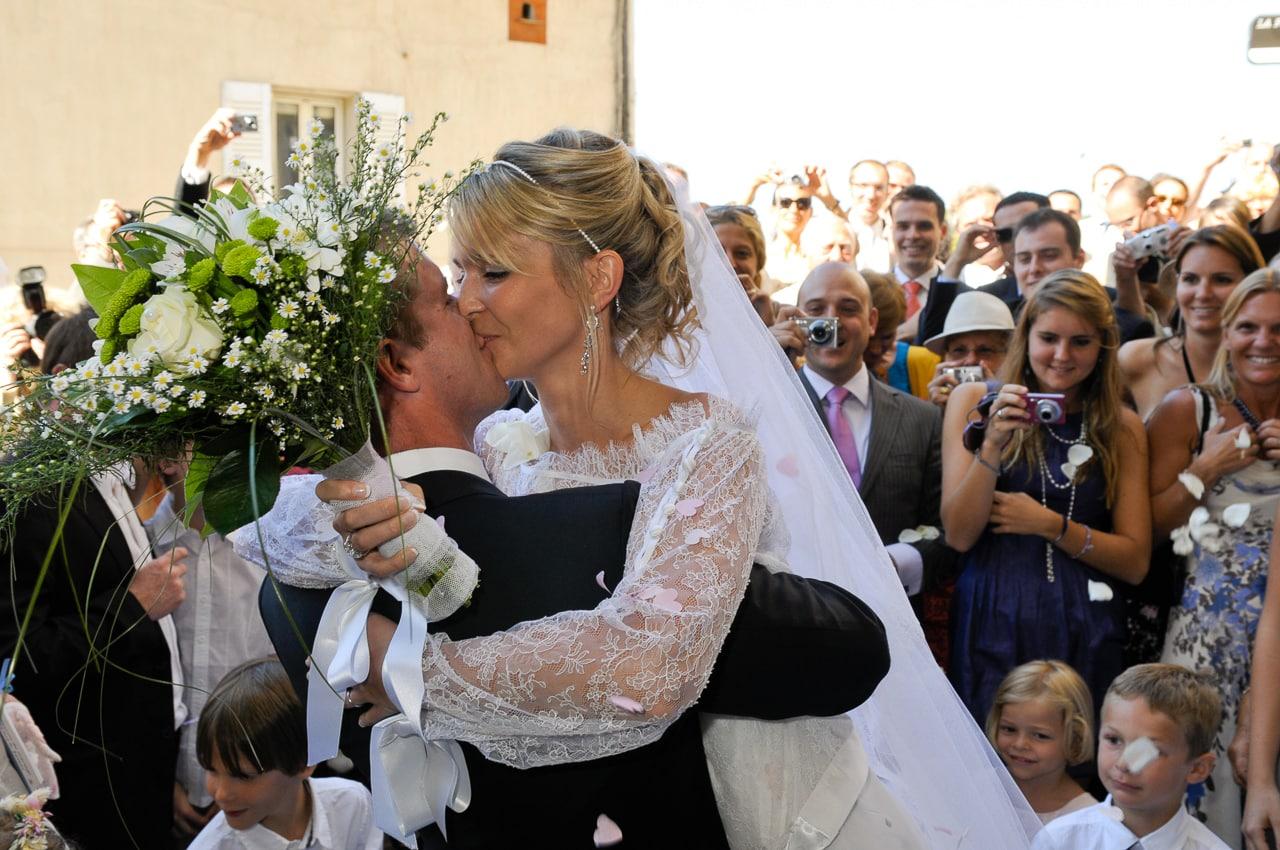 Mariés s'embrassant devant les invités du mariage