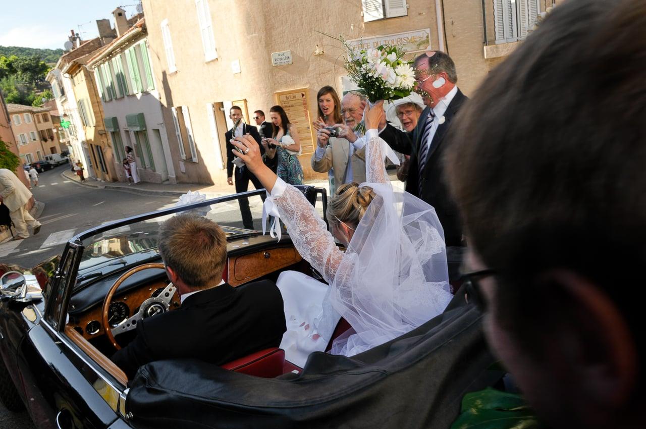 Mariés heureux dans leur voiture en ville