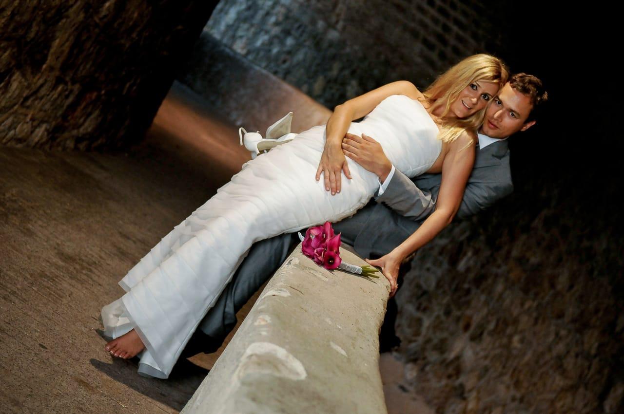 Mariée assise sur le marié sur un rebord en pierre