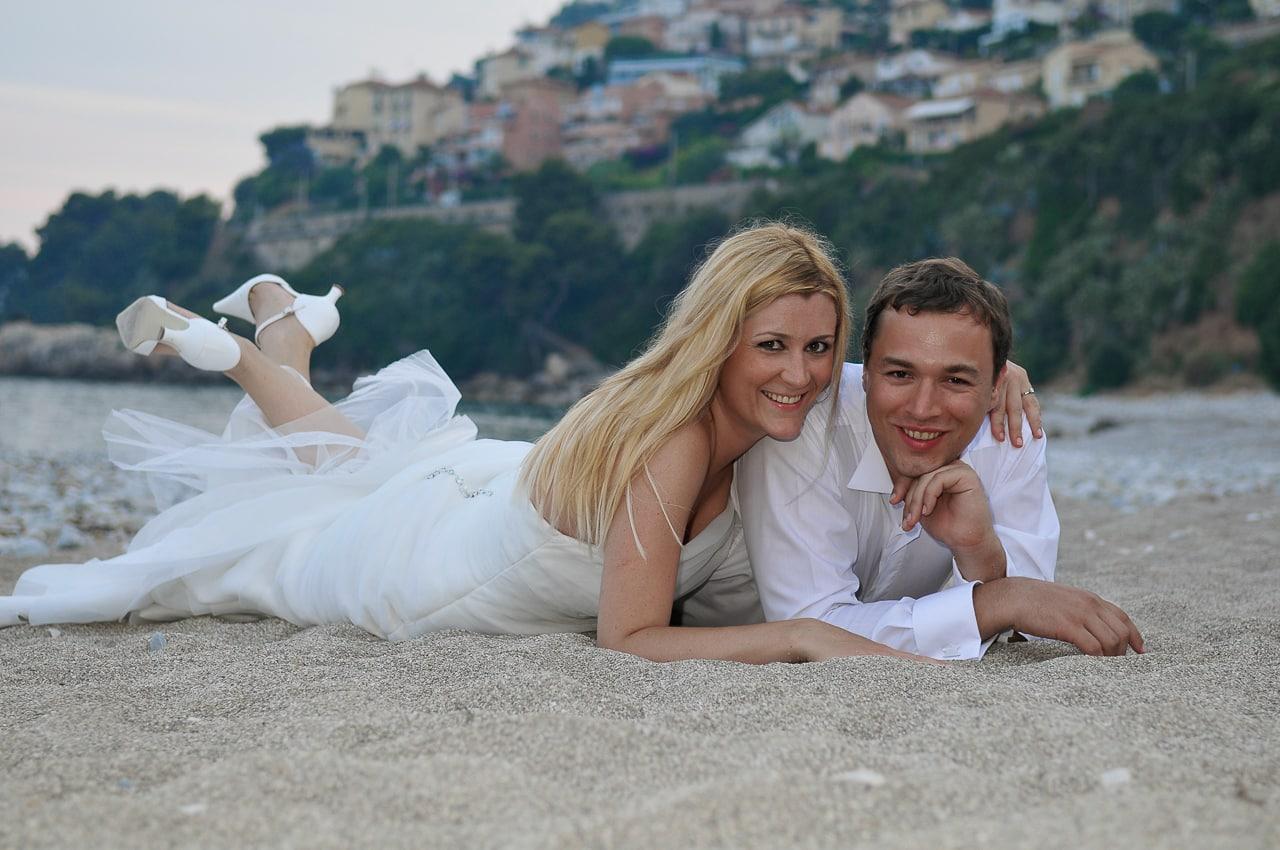 Mariés souriants et allongés sur le sable